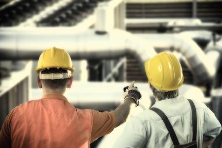 Arbeiter in Schutzkleidung und Schutzhelm vor Industrierohren
