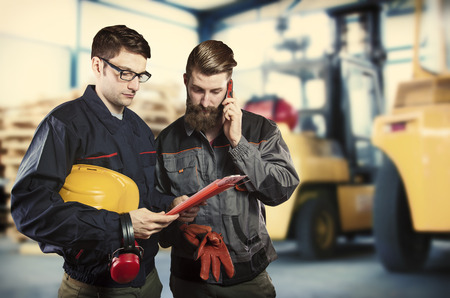 ear muff: Workers in protective uniform in front of forklift