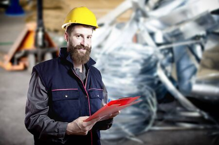 Smiling worker in protective uniform and protective helmet in production hall in front of steel sheet metal scrap  Stock Photo
