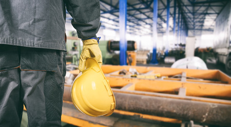 steel workers: worker with protective uniform in production hall  Stock Photo