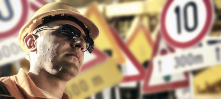 ear muff: Worker in protective uniform and protective helmet in front of road signs Stock Photo