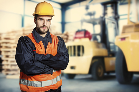 extrusion: Worker in protective uniform in front of forklift