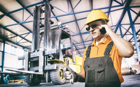 extrusion: Worker in protective uniform in production hall in front of forklift