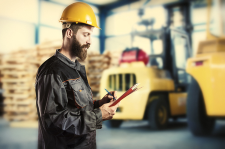 muff: Worker in protective uniform in front of forklift  Stock Photo