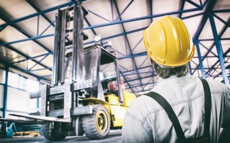 carretillas almacen: Trabajador en uniforme protector en la nave de producción frente a la carretilla elevadora