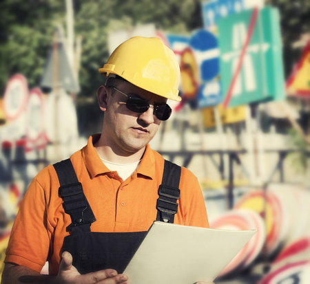 engineering clipboard: Worker in protective uniform and protective helmet in front of road signs Stock Photo