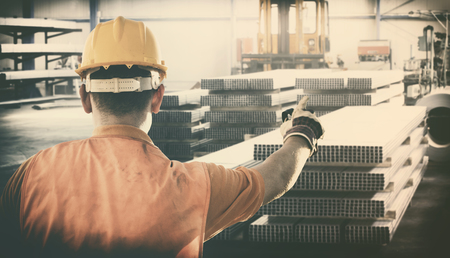 extrusion: worker with protective uniform in front of metal proflies  Stock Photo