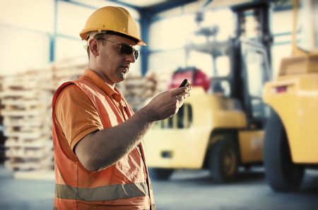 ear muff: Worker in protective uniform in front of forklift