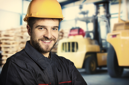happy workers: Smiling worker in protective uniform in front of forklift  Stock Photo