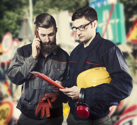 ear muff: Workers in protective uniforms and in front of road signs
