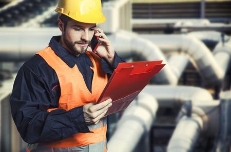 Trabajador en uniforme de protección con teléfono inteligente y portapapeles delante de tuberías industriales Foto de archivo