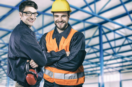 engineering clipboard: Smiling workers in protective uniforms in production hall Stock Photo