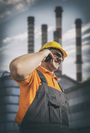 engineering clipboard: Smiling worker in protective uniform in front of industrial chimney