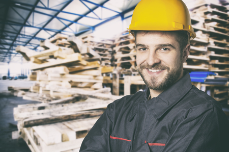 muff: Smiling worker in protective uniform in front of wooden pallets Stock Photo