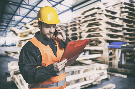 Worker in protective uniform in front of wooden pallets