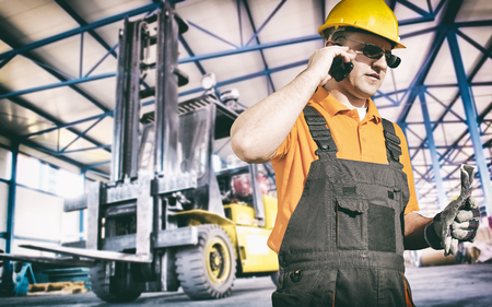 ear muff: Worker in protective uniform in production hall in front of forklift