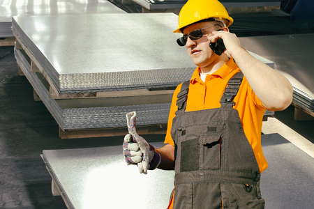 ear muff: Worker in protective uniform in front of sheet tin metal Stock Photo