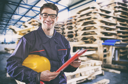 extrusion: Smiling worker in protective uniform in front of wooden pallets Stock Photo