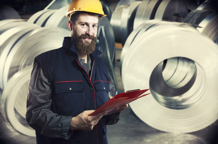 engineering clipboard: smiling worker in protective uniform and protective helmet in front of sheet tin metal rolls in production hall