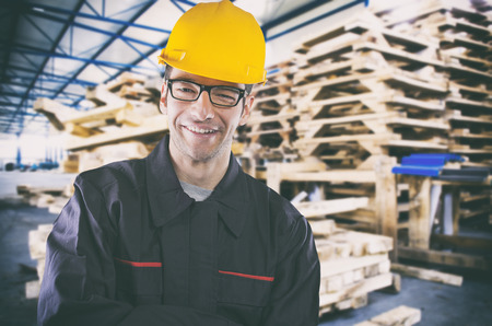 ear muff: Smiling worker in protective uniform in front of wooden pallets Stock Photo