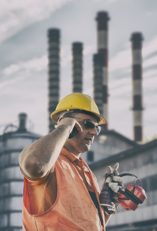 engineering clipboard: Worker in protective uniform in front of industrial chimney