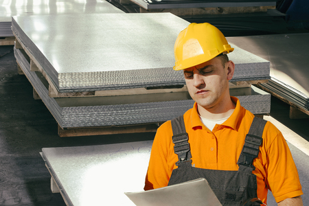 engineering clipboard: Worker in protective uniform in front of sheet tin metal Stock Photo