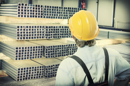 steel sheet: worker in protective uniform and protective helmet in production hall in front of steel sheet metal profiles Stock Photo