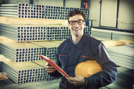 engineering clipboard: smiling worker in protective uniform and protective helmet in production hall in front of steel sheet metal profiles Stock Photo