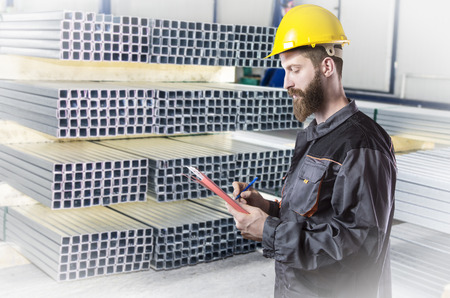 extrusion: worker in protective uniform and protective helmet in production hall in front of steel sheet metal profiles Stock Photo