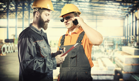 engineering clipboard: workers in protective uniforms with smart phone, clipboard, protective helmet, protective gloves, and ear muffs in their hands in production hall