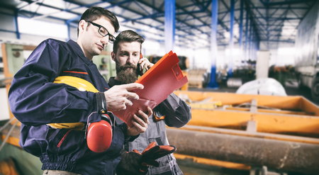 ear muff: workers with protective uniforms in production hall Stock Photo