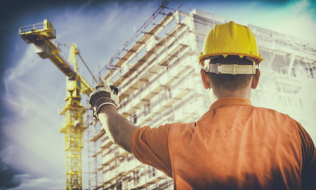 ear muff: worker with protective uniform in front of construction scaffolding and construction crane