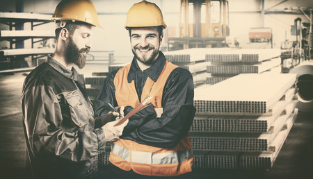 Smiling workers with protective uniforms in front of metal proflies Stock Photo