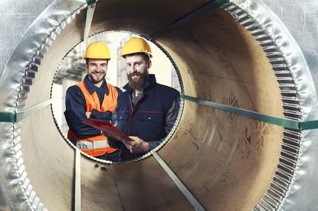 steel sheet: smiling workers seen through a steel sheet metal roll