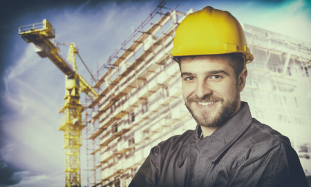 ear muff: Smiling worker with protective uniform in front of construction scaffolding and construction crane
