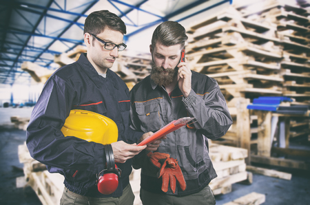 engineering clipboard: Workers in protective uniform in front of wooden pallets