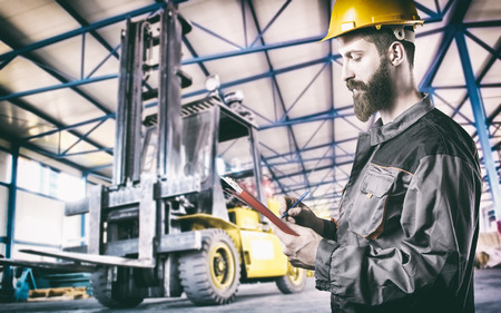 Worker in protective uniform in production hall in front of forklift