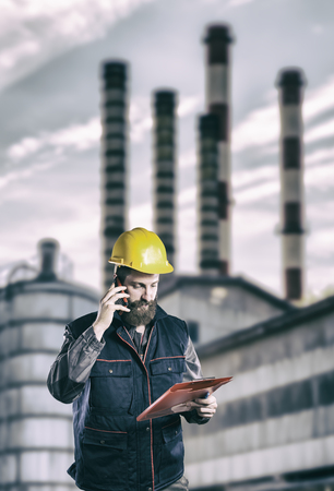 ear muff: Worker in protective uniform in front of industrial chimney  Stock Photo