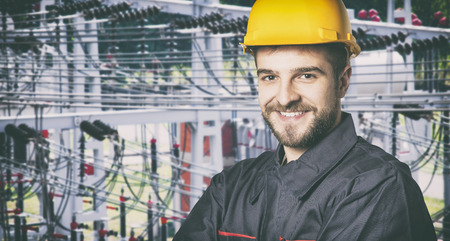 ear muff: Smiling worker with protective uniform in front of power plant  Stock Photo