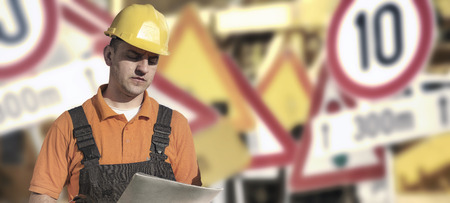 muff: Worker in protective uniform and protective helmet in front of road signs