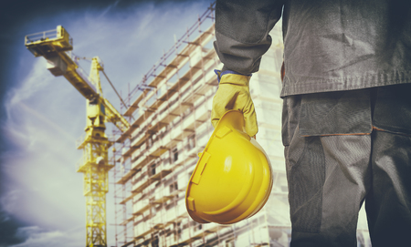 muff: worker with protective uniform in front of construction scaffolding and construction crane