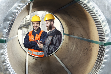steel sheet: smiling workers seen through a steel sheet metal roll  Stock Photo