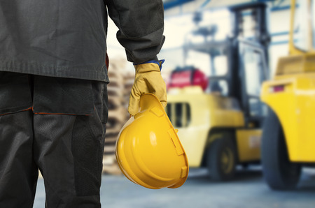ear muff: Worker in protective uniform in front of forklift  Stock Photo