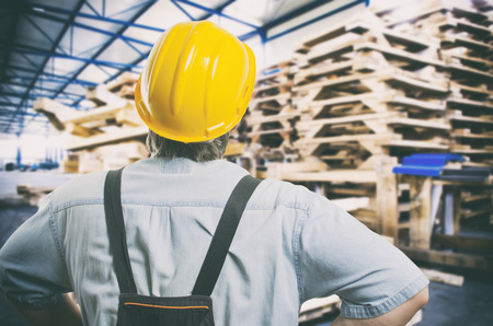 engineering clipboard: Worker in protective uniform in front of wooden pallets