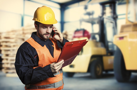 engineering clipboard: Worker in protective uniform in front of forklift  Stock Photo