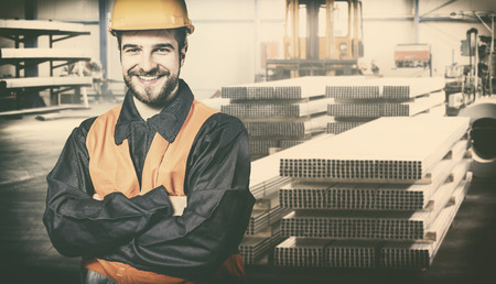 extrusion: Smiling worker with protective uniform in front of metal proflies
