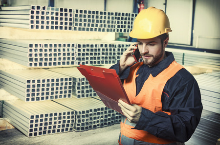 engineering clipboard: worker in protective uniform and protective helmet in production hall in front of steel sheet metal profiles Stock Photo