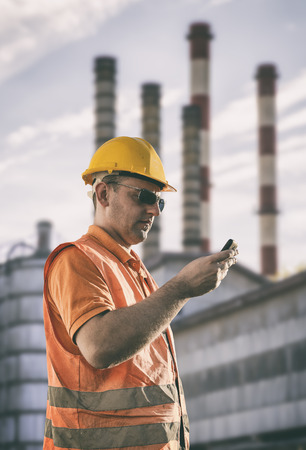 engineering clipboard: Worker in protective uniform in front of industrial chimney  Stock Photo
