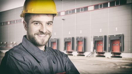 Smiling worker with protective uniform in front of shipping warehouse gates