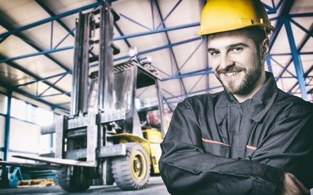 extrusion: Smiling worker in protective uniform in production hall in front of forklift  Stock Photo